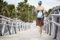 Spain, back view of young woman with blue dyed hair with backpack hopping on a bridge - ERRF00147