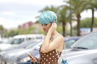 Spain, young woman with blue dyed hair  listening music with earphones and smartphone - ERRF00150
