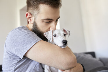Man cuddling his dog at home - ZEDF01774