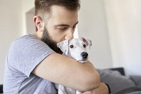 Man cuddling his dog at home - ZEDF01774