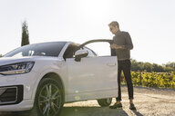 Italy, Tuscany, Siena, young man getting out of car in a vineyard - FBAF00190