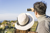 Italy, Tuscany, Siena, young couple taking a selfie at a winery - FBAF00193