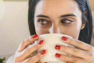 Close-up portrait of beautiful young woman drinking cup of coffee - FBAF00202