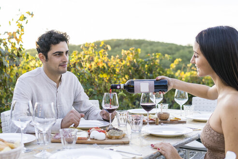 Italy, Tuscany, Siena, young couple having dinner in a vineyard with red wine - FBAF00205