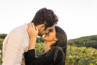 Italy, Tuscany, Siena, happy young couple kissing in a vineyard - FBAF00214