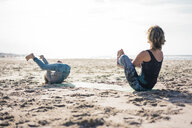 Mother and daughter practising yoga on the beach - MOEF01566