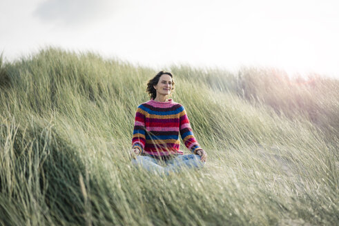 Mature woman relaxing on the beach, sitting in the dunes - MOEF01575