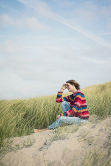 Mature woman relaxing on the beach, sitting in the dunes - MOEF01578