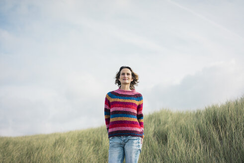 Content woman standing in the dunes, smiling - MOEF01581