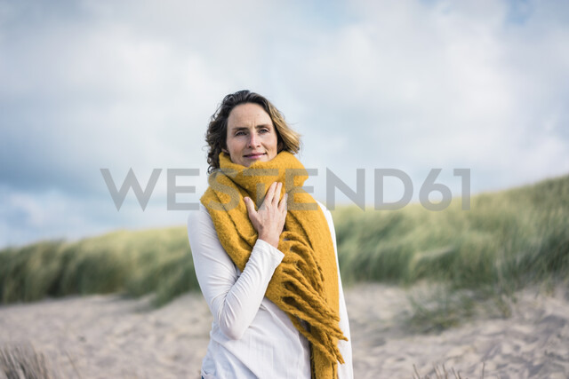 Mature woman relaxing in the dunes, enjoying the wind - MOEF01587 - Robijn Page/Westend61
