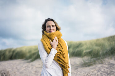 Mature woman relaxing in the dunes, enjoying the wind - MOEF01587