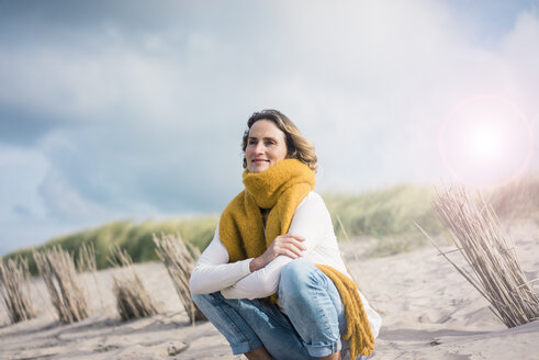 Mature woman crouching in the dunes, enjoying the wind - MOEF01590