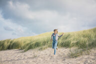 Happy girl having fun on the beach, running in the dunes - MOEF01596