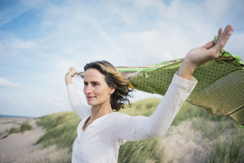 Mature woman holding flapping scarf in the wind, relxiang in the dunes - MOEF01602