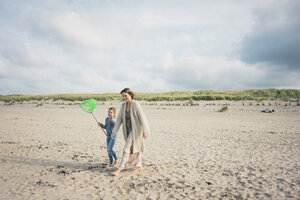 Mother and daughter walking to the sea with a dip net - MOEF01605