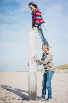 Mature man helping woman to climb a wood pole on he beach - MOEF01614