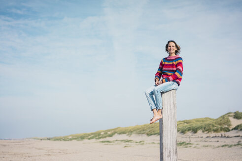 Mature woman sitting on a wood pole on the beach - MOEF01617