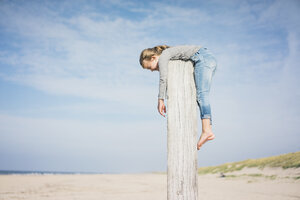 Little girl on the beach hanging on a pole - MOEF01620