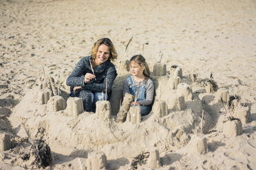 Mother and daughter building a sandcastle on the beach - MOEF01623