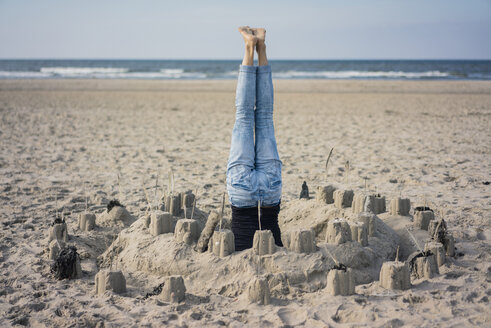 Mature woman doing a headstand on the beach in a sandcastle - MOEF01626