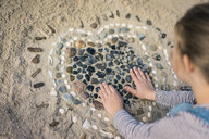 Little girl making a heart from seashells on the beach - MOEF01629