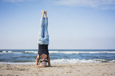 Mature woman doing a headstand on the beach - MOEF01632