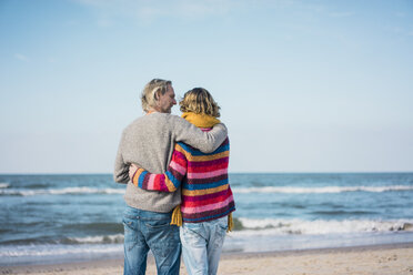 ture couple standing on the beach with arms around, looking at the sea - MOEF01635