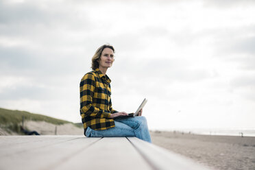 Mature woman sitting on boardwalk at the beach, using laptop - MOEF01638