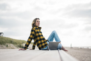 Mature woman sitting on boardwalk at the beach, using laptop - MOEF01641