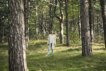 Serene woman standing in the forest - MOEF01650