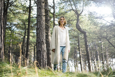 Serene woman standing in the forest - MOEF01653
