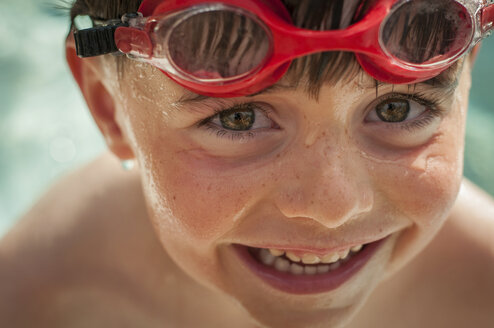 High angle portrait of shirtless cute boy with swimming goggles - CAVF56038