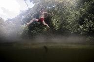 Low angle view of shirtless energetic man diving into lake at forest - CAVF56083