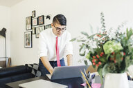 Businessman using laptop computer while working in office - CAVF56107