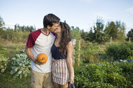 Young couple kissing while standing against sky at community garden - CAVF56236