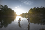 Side view of male friends fishing while standing in lake against sky during sunset - CAVF56287