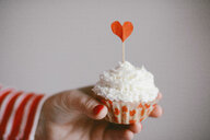 Cropped hand of woman holding cupcake against wall at home - CAVF56383