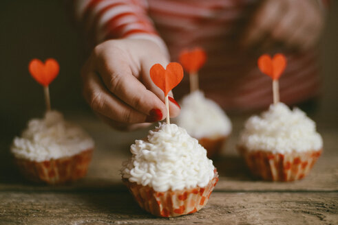 Midsection of woman decorating cupcakes on wooden table at home - CAVF56386