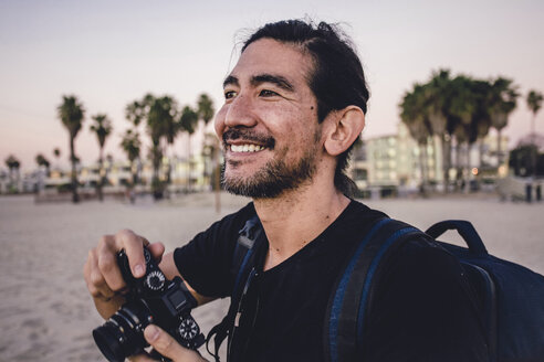 Close-up of smiling backpacker holding camera while looking away at beach - CAVF56398