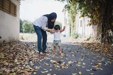 Mother assisting son in walking on street - CAVF56407