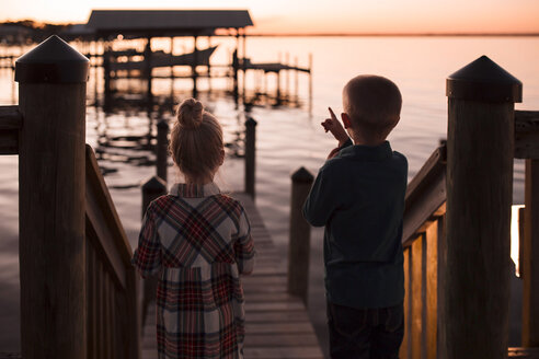 Rear view of brother pointing towards lake while standing by sister during sunset - CAVF56413