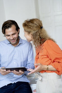 Happy couple working from home, discussing over digital tablet - HHLMF00558