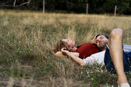 Happy couple cuddling, lying on a meadow - HHLMF00570