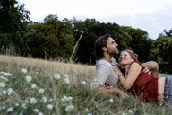 Happy couple cuddling, lying on a meadow - HHLMF00576