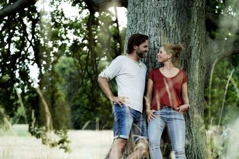 Happy couple leaning on a tree, smiling at each other - HHLMF00615