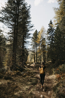Switzerland, Engadin, woman on a hiking trip in forest - LHPF00131