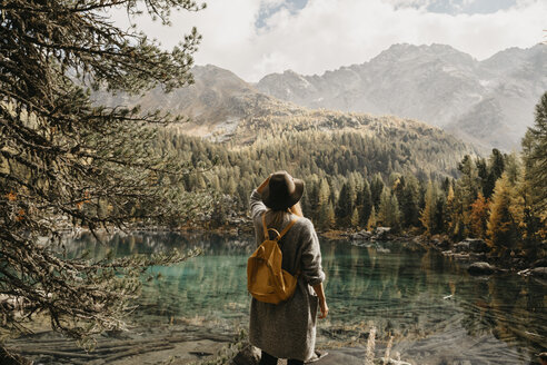 Switzerland, Engadin, woman on a hiking trip standing at lakeside in mountainscape - LHPF00134