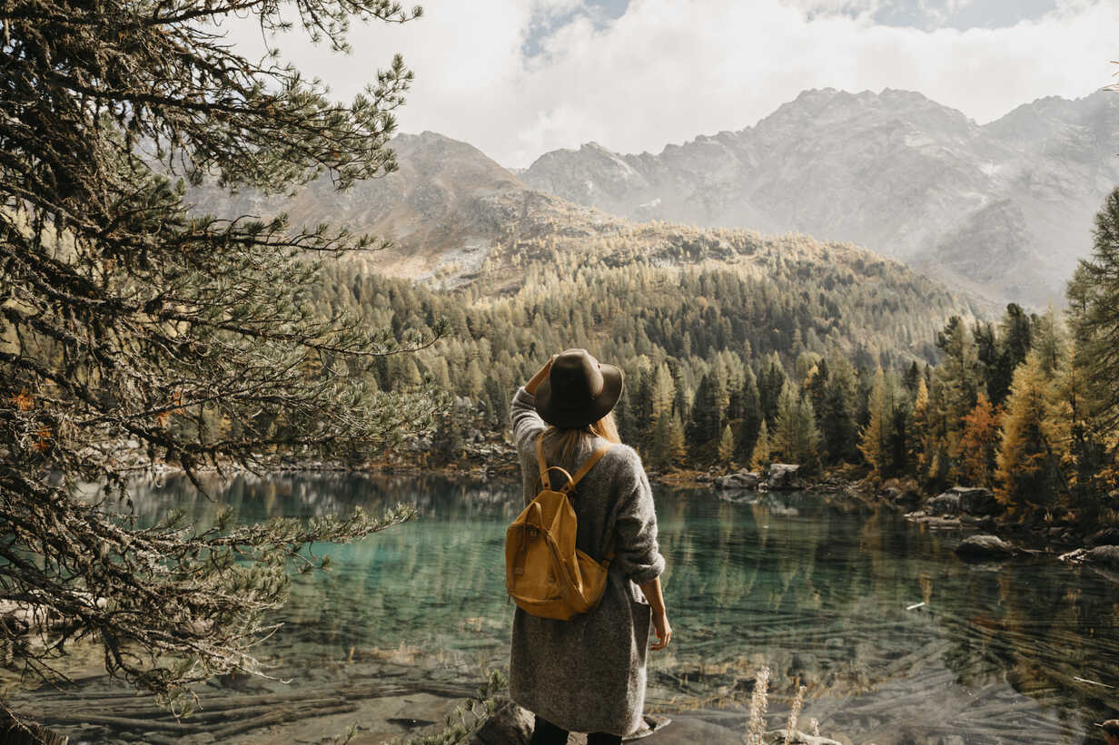 Switzerland, Engadin, woman on a hiking trip standing at lakeside in mountainscape - LHPF00134 - letizia haessig photography/Westend61