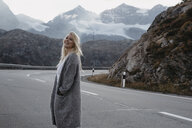 Switzerland, Engadin, happy young woman standing at the roadside in mountainscape - LHPF00137