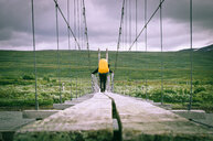 Rear view of a man walking over a bridge under a cloudy sky - INGF07828